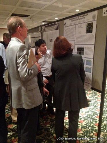 Andrew Kau discusses poster with a group of poster judges